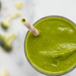 top down view of a green broccoli smoothie with broccoli next to it