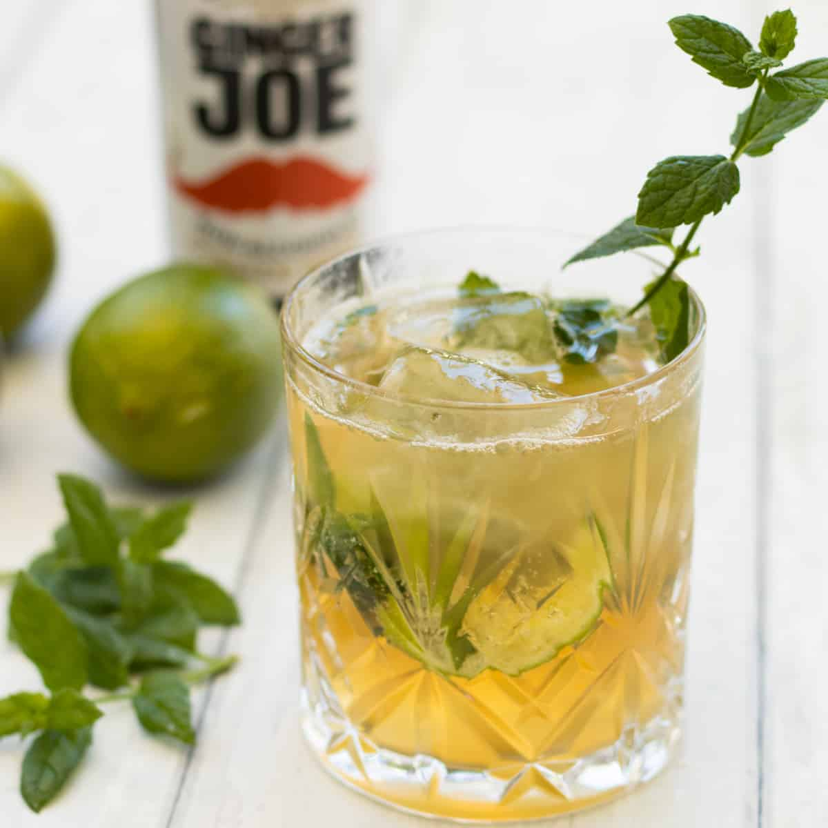 ginger beer mocktail decorated with a sprig of mint with a bottle of ginger beer in the background