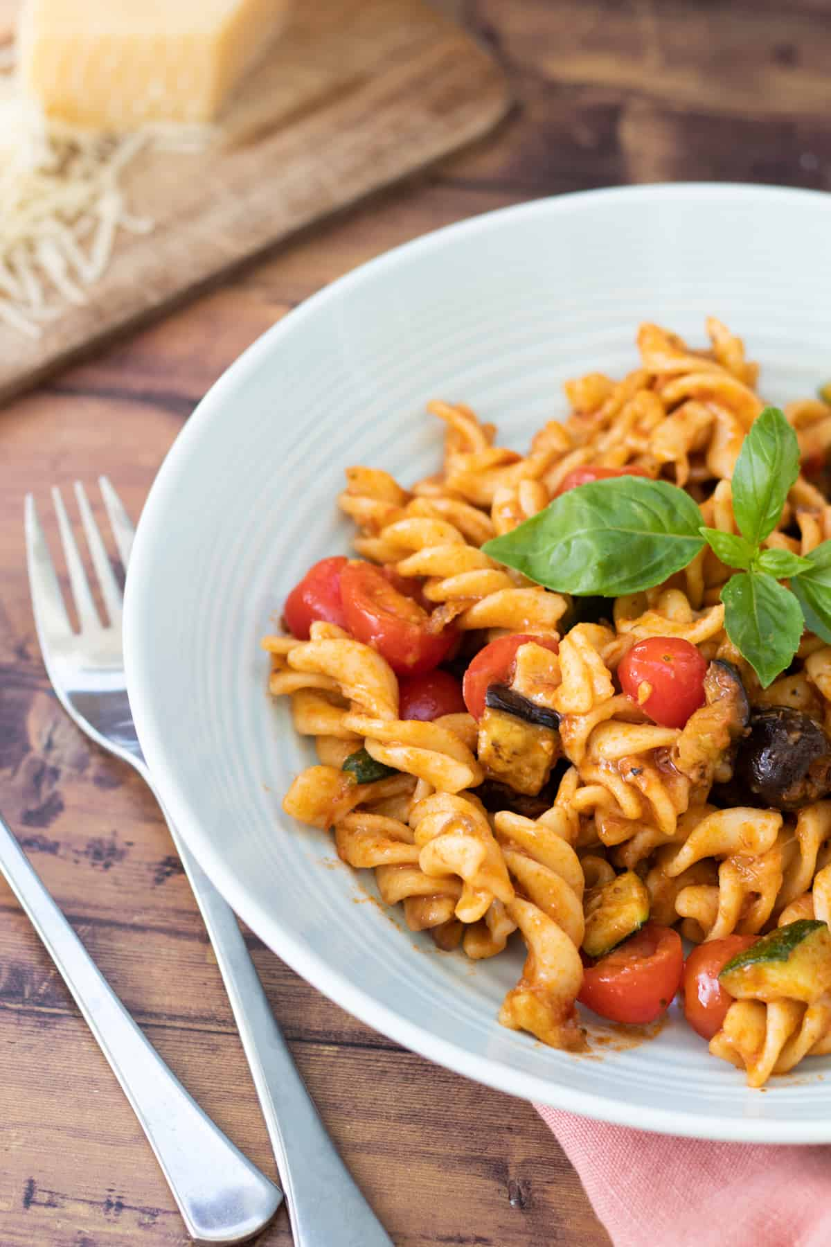 a bowl full of red pesto pasta topped with basil leaves