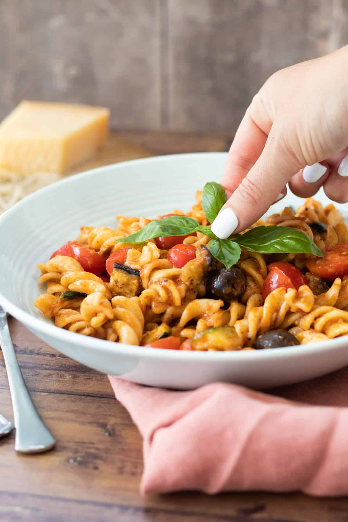 a bowl of red pesto pasta being topped with basil leaves