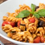 close up of a bowl full of red pesto pasta topped with basil leaves