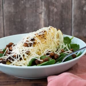 sweetheart cabbage salad topped with parmesan cheese in a light blue bowl