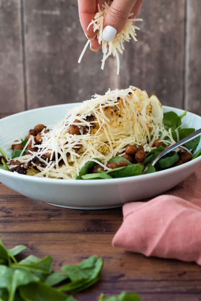 parmesan cheese being dropped over a sweetheart cabbage salad