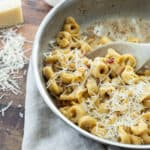 tortellini carbonara in a pan topped with cheese