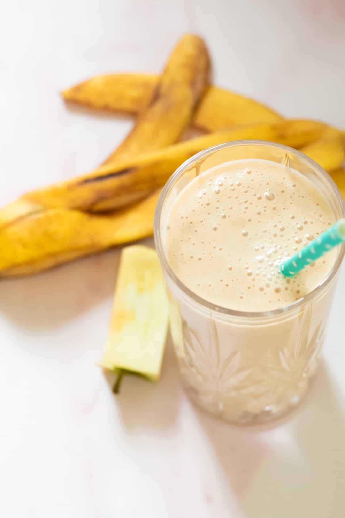 an apple banana smoothie with banana peel and apple core in the background