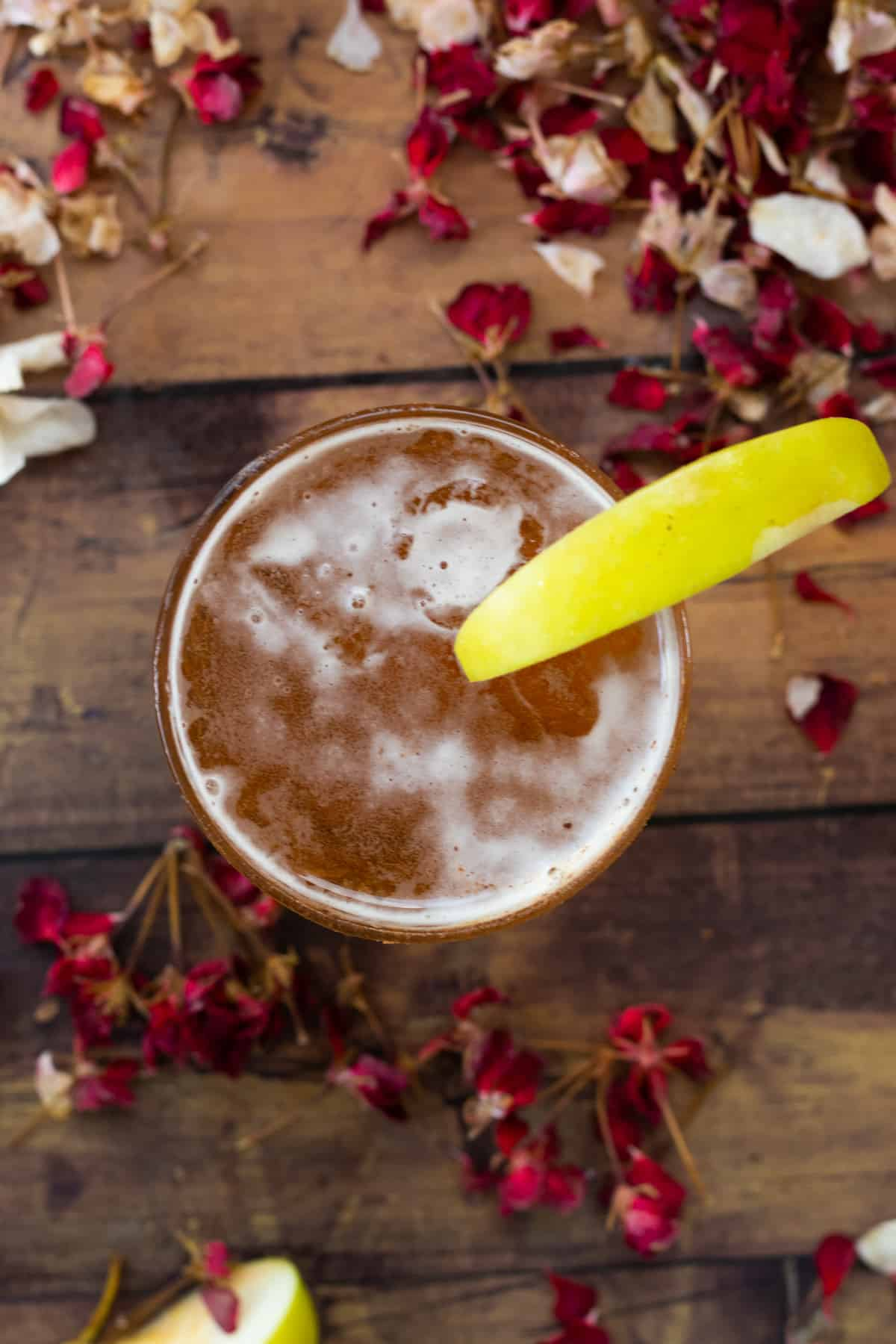 top down view of an apple cider cocktail decorared with an apple wedge