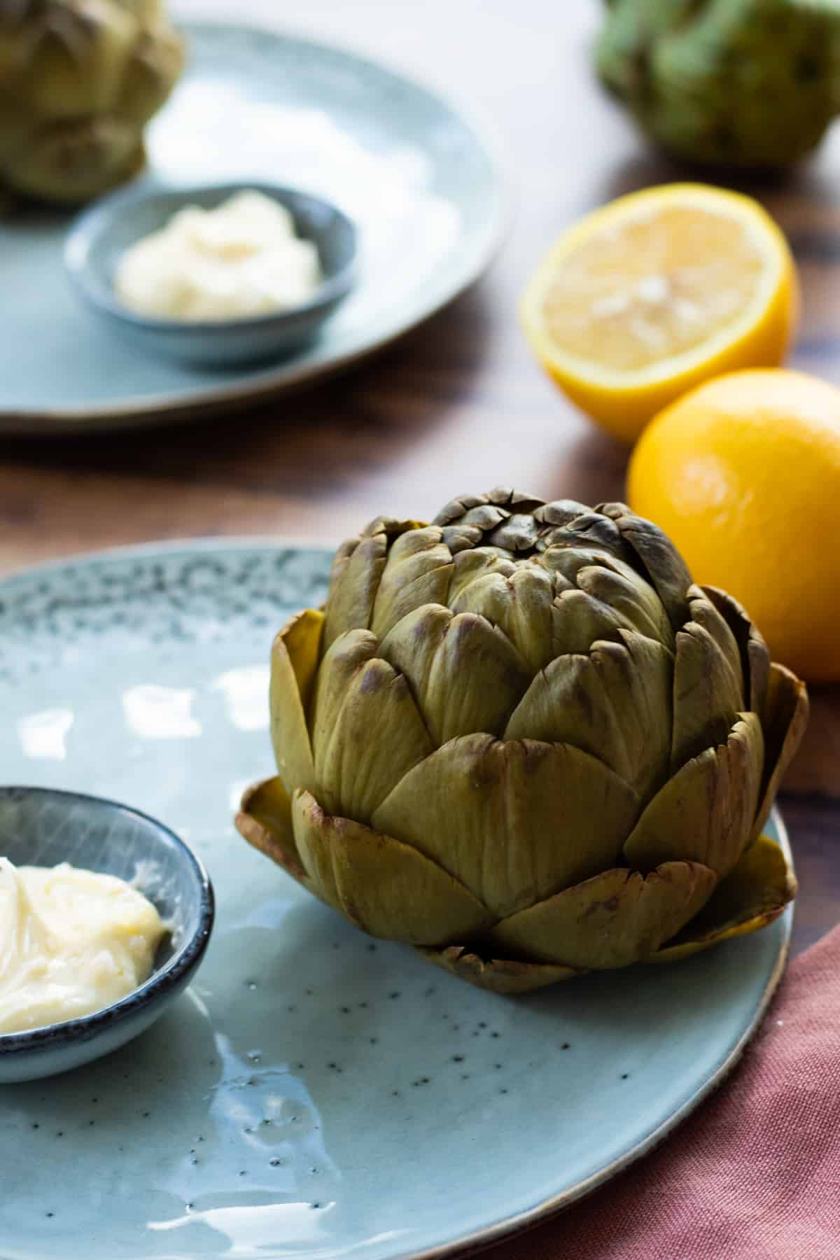 a cooked artichoke on a blue plate next to a bowl of whipped lemon butter