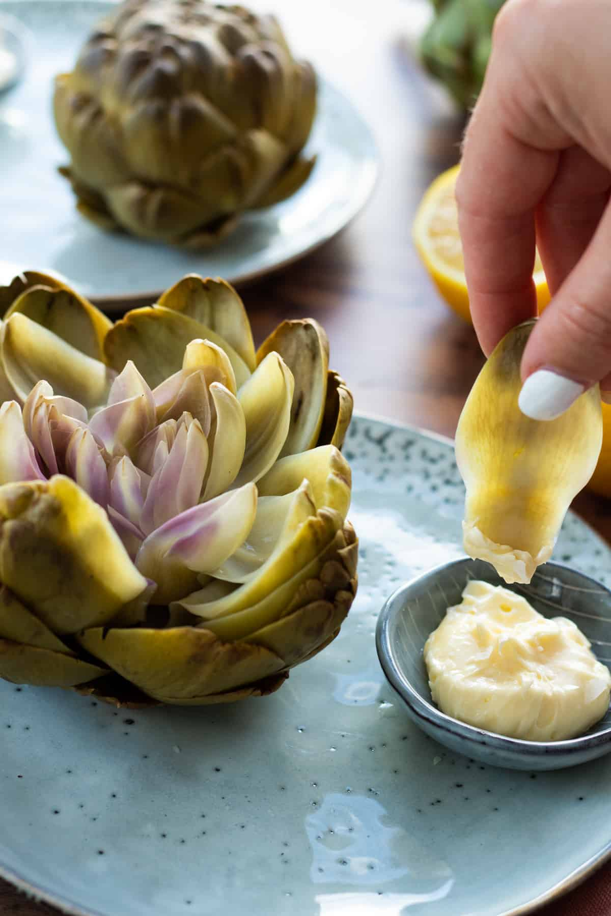 an artichoke leaf being dipped into whipped lemon butter next to a whole artichoke