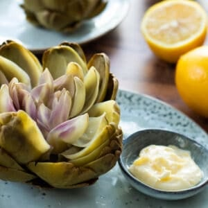 side view of a boiled artichoke on a blue plate