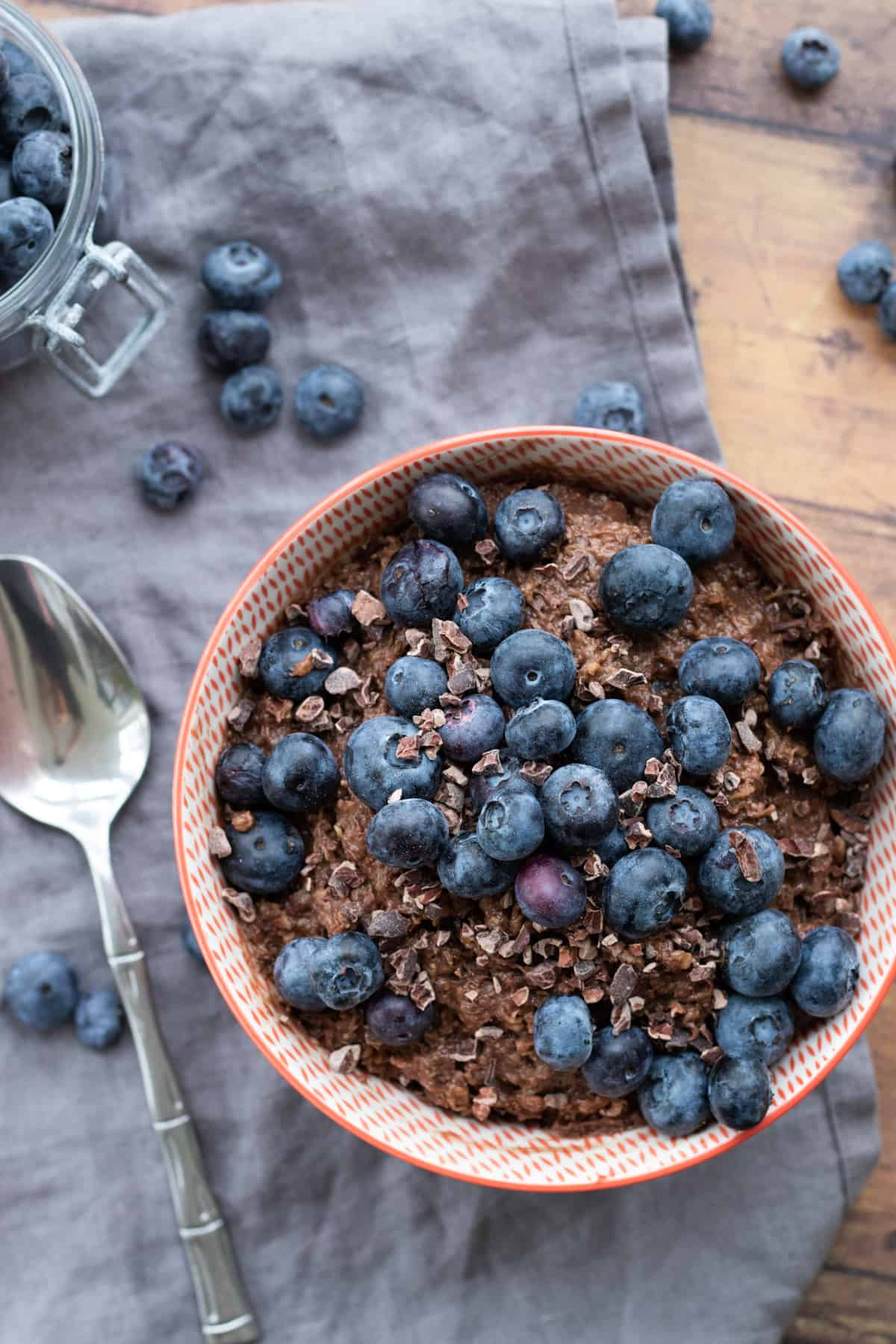 top down view of a bowl of chocolate oatmeal topped with blueberries