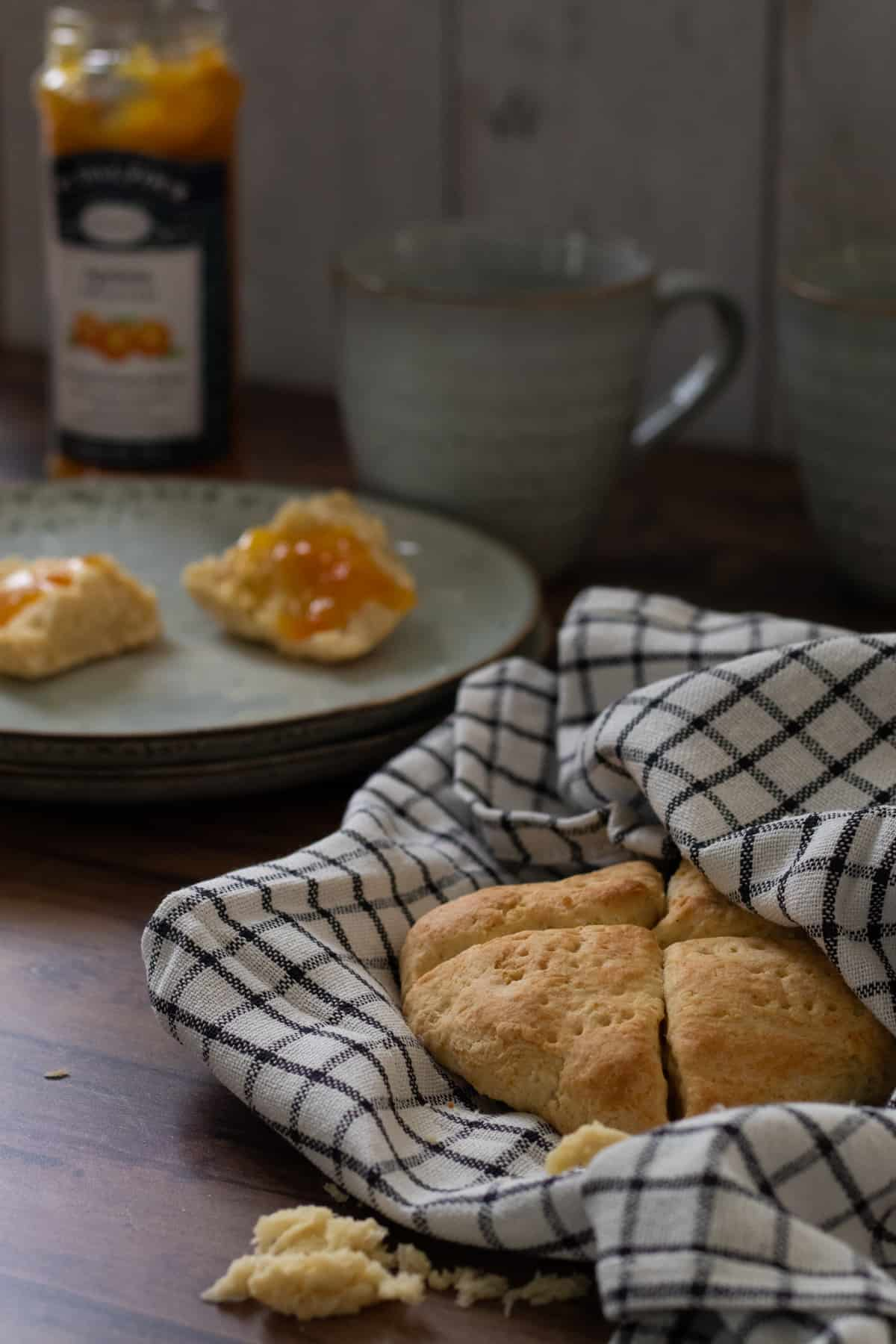 scones in a kitchen towel with some scones topped with marmalade in the background
