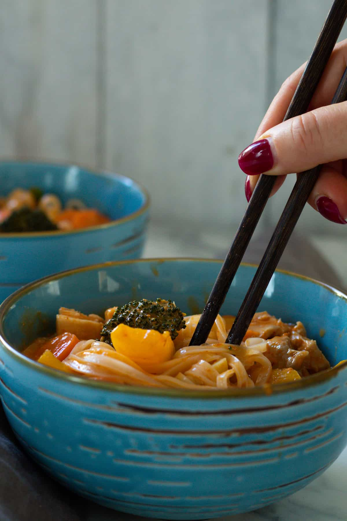 chopsticks swirling around in a bowl of spicy chicken noodle soup