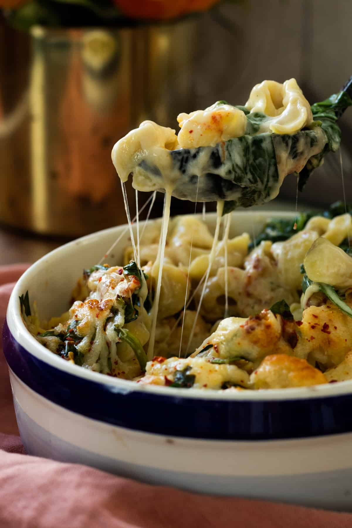 a spoonful of tortellini and spinach being lifted out of a dish full