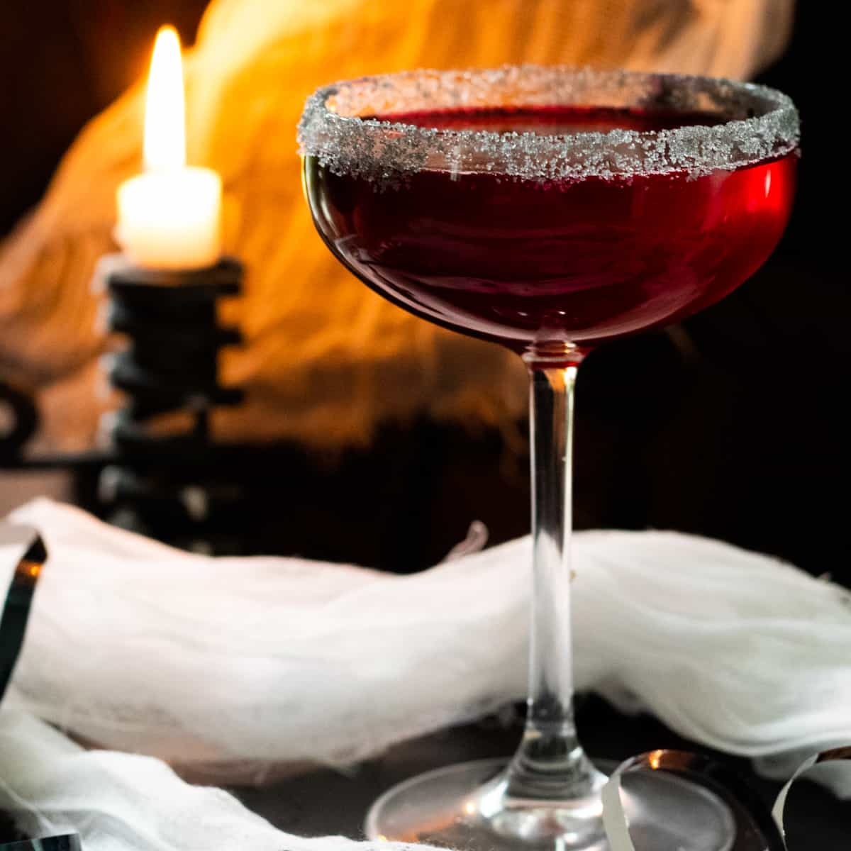vampire margarita with a candle and cob webs in the background