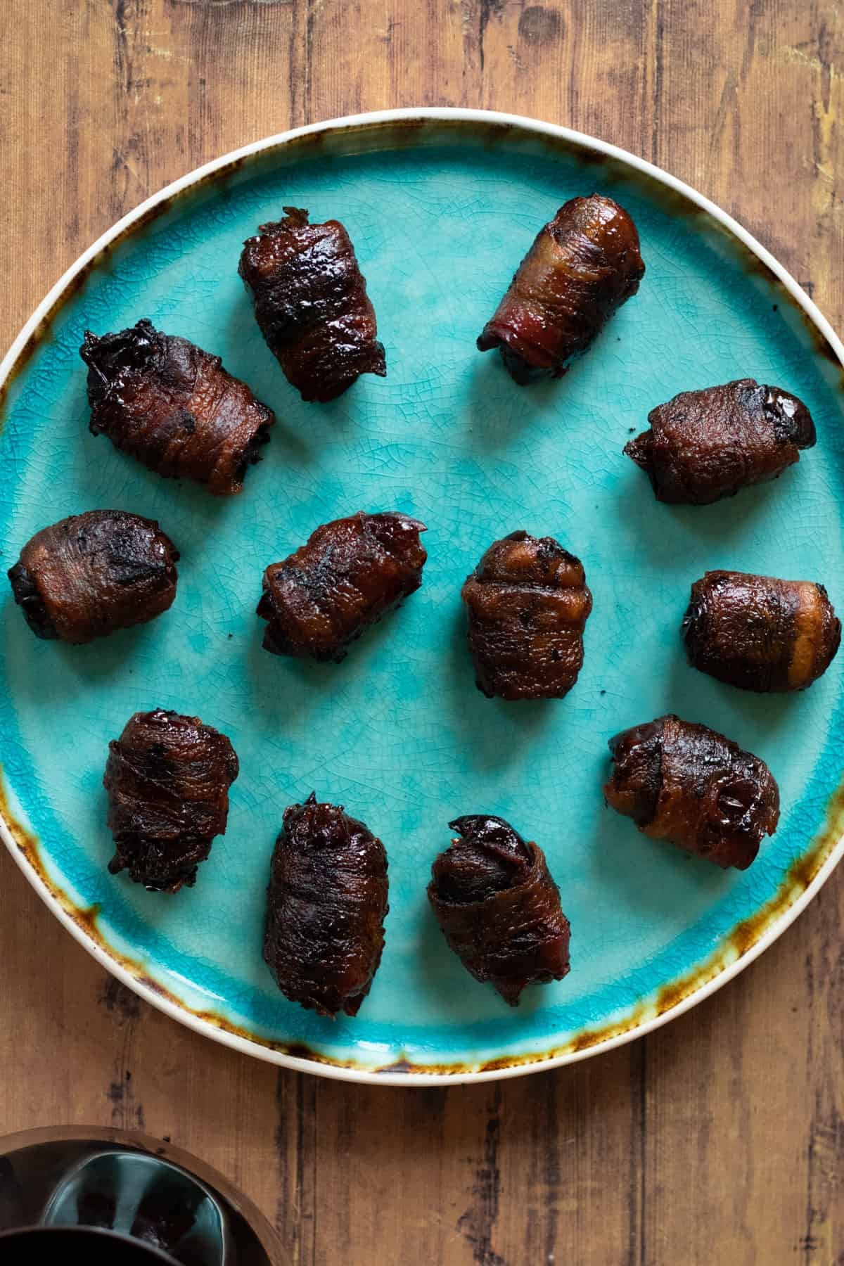 top down view of bacon wrapped dates on a plate