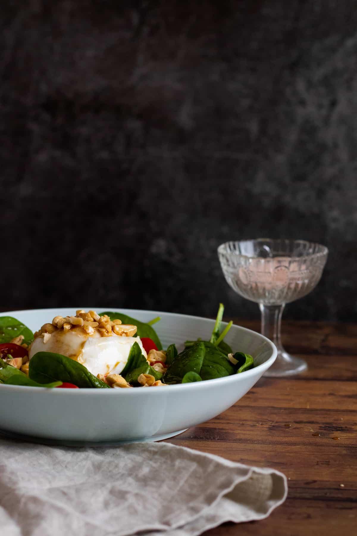 sidew view of a burrata caprese salad on a light blue deep plate