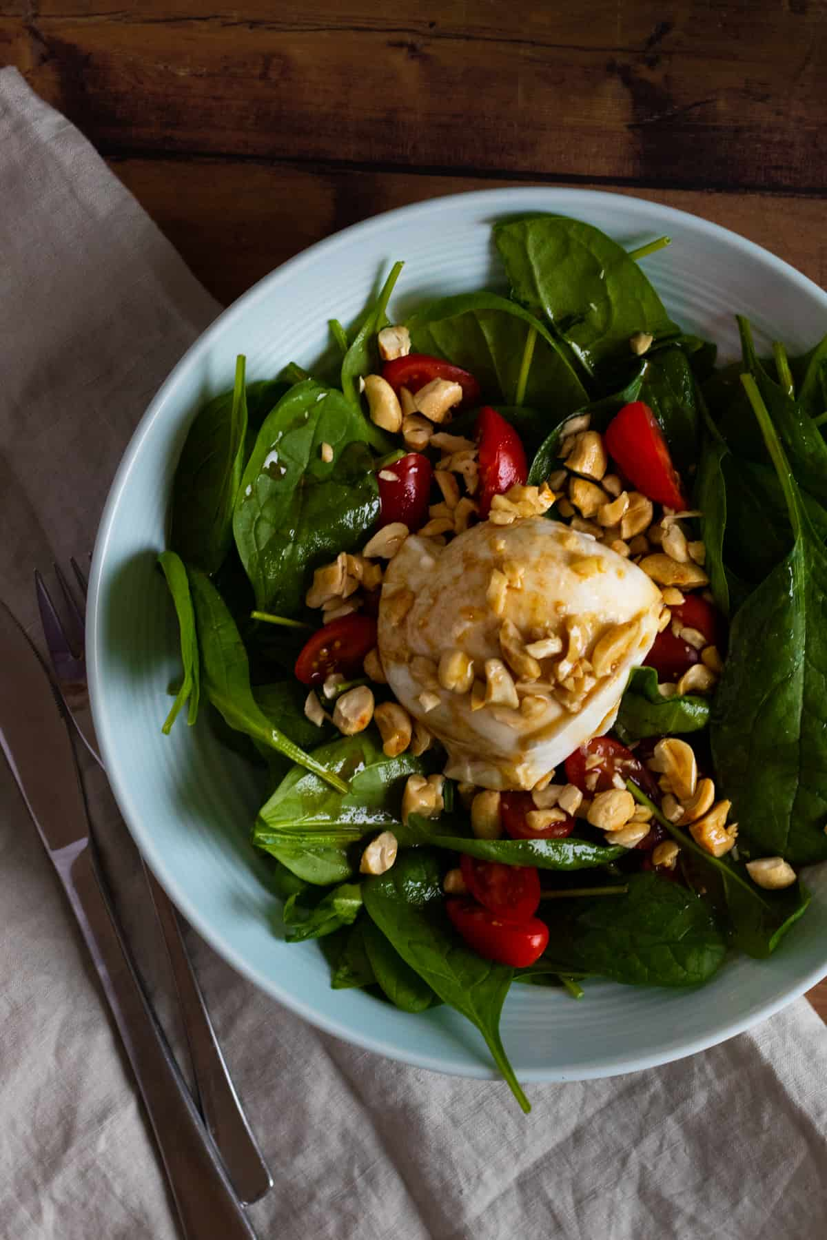 top down view of a burrata caprese salad topped with cashew nuts