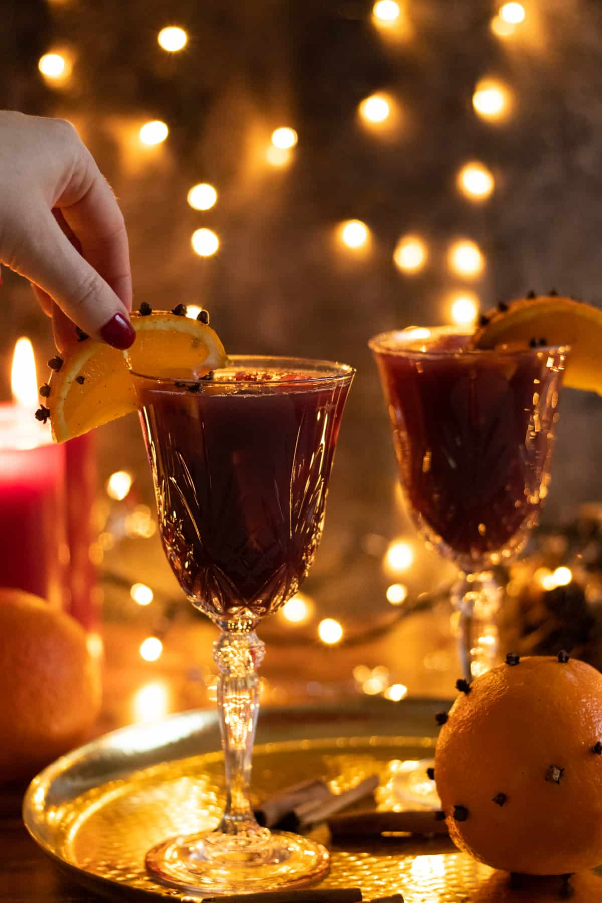 an orange wedge being placed on a glass of christmas sangria