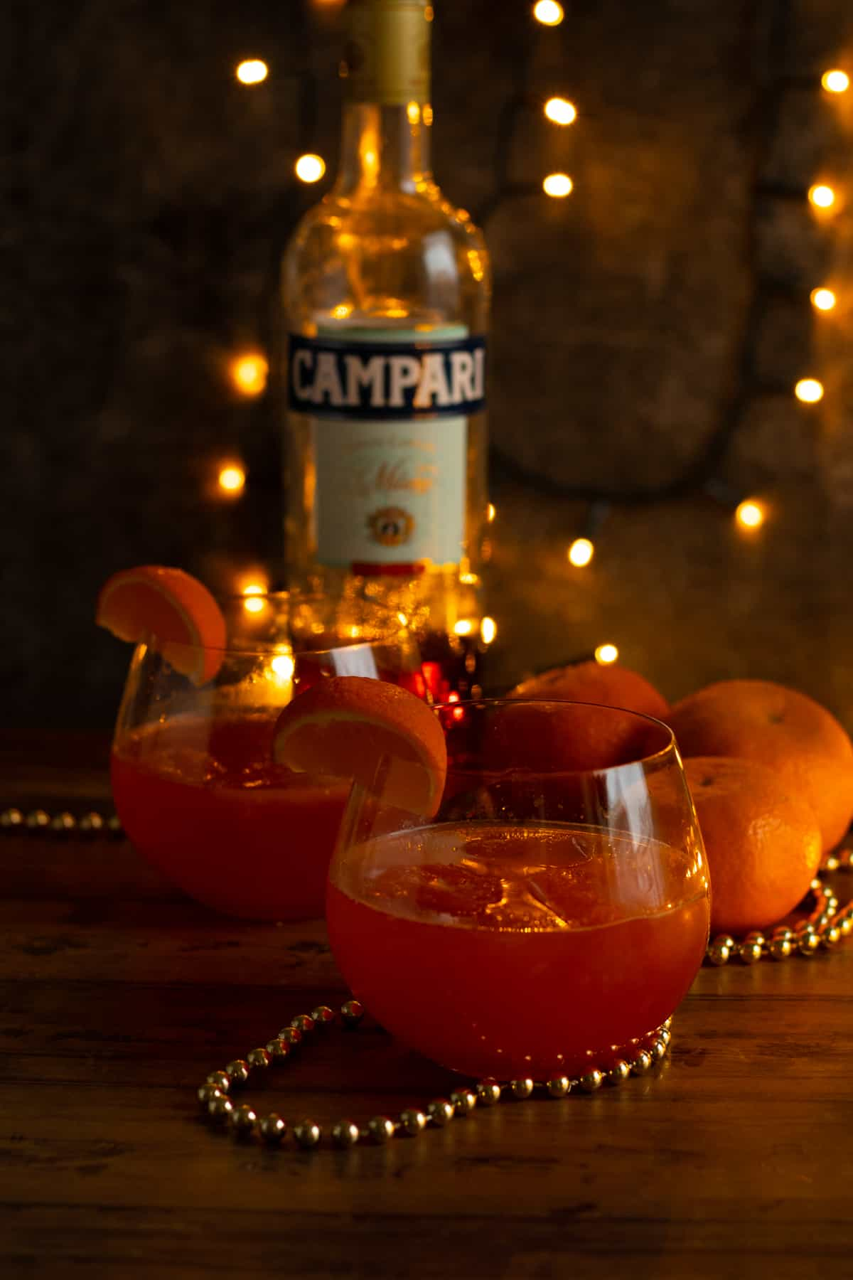 twoclementine campari spritzes with clementines and a bottle of campari in the background