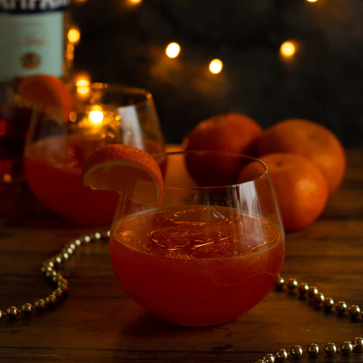 a clementine campari spritz with clementines and a bottle of campari in the background