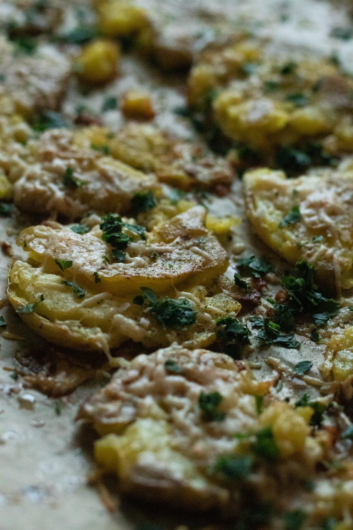 closeup garlicky smashed potatoes on a baking tray
