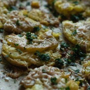 closeup of garlicky smashed potatoes on a baking tray