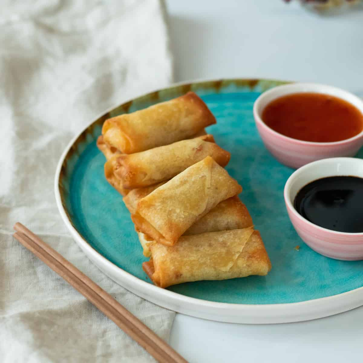 air fryer spring rolls on a blue plate next to two sauces
