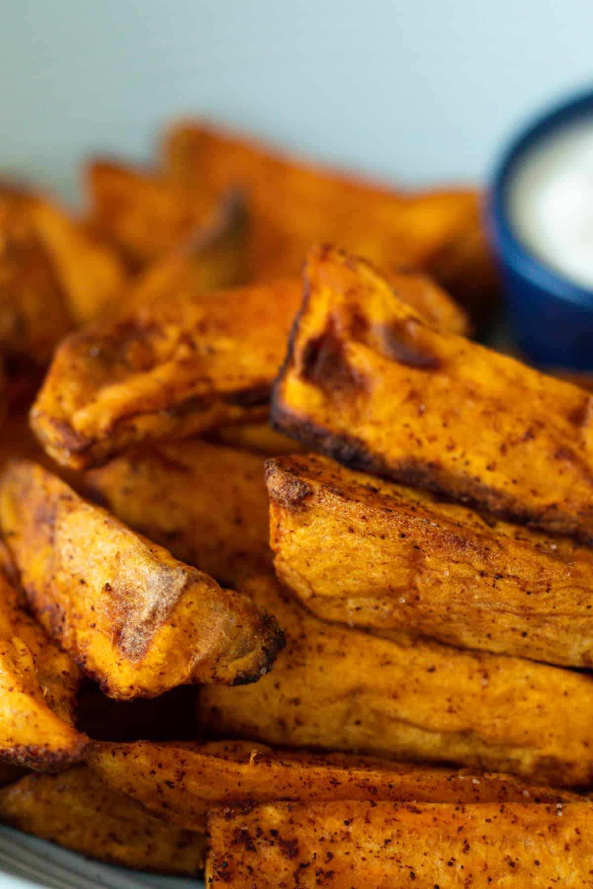 air fryer sweet potatoes on a plate with a white dip
