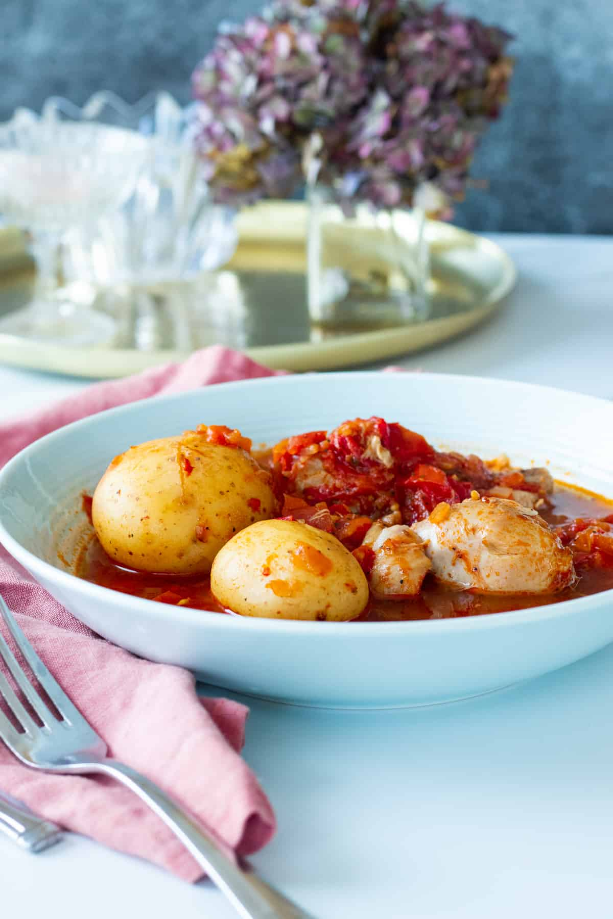 chicken and potatoes with tomato sauce in a blue bowl
