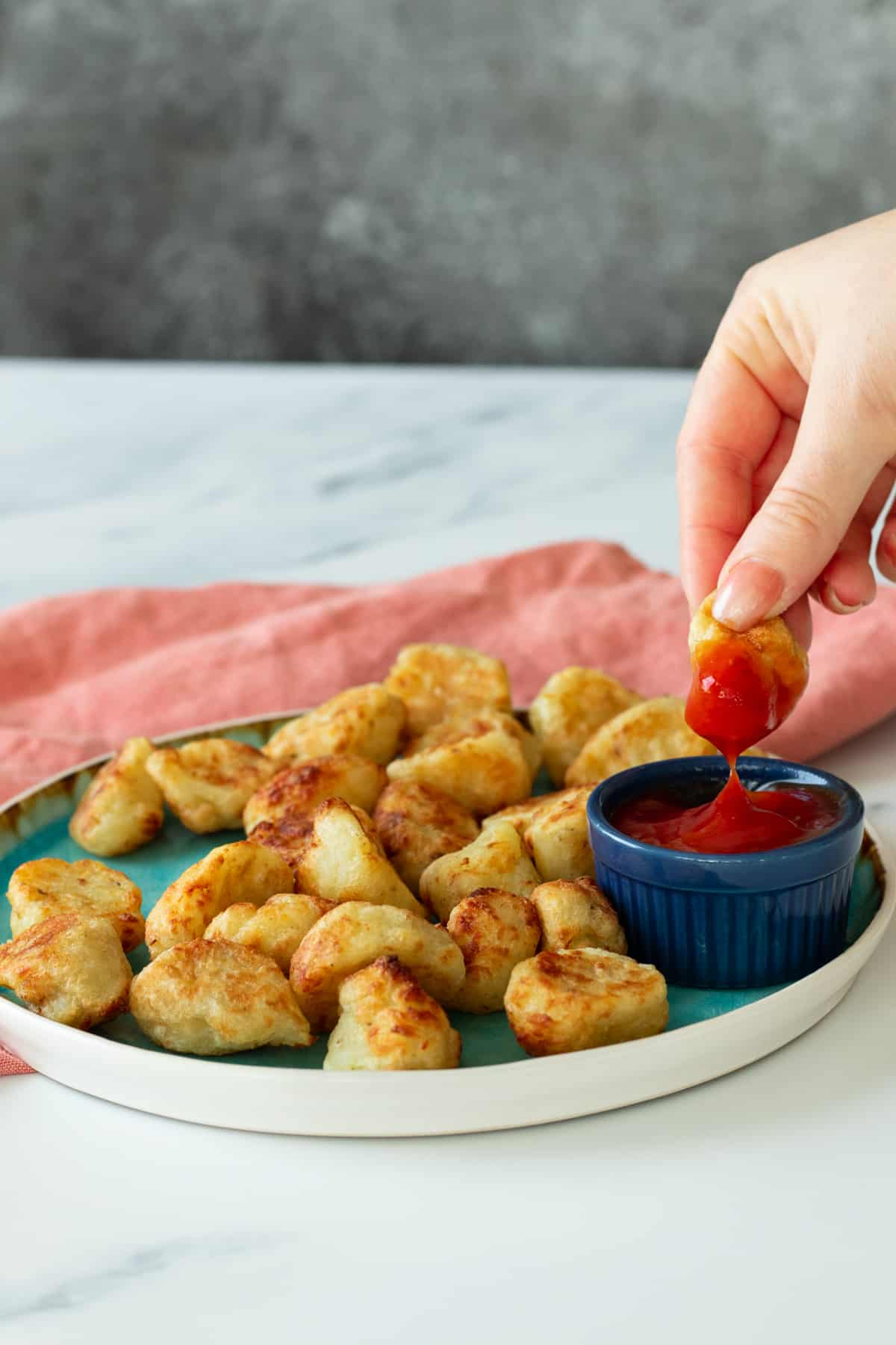 a tater tot dipped in ketchup