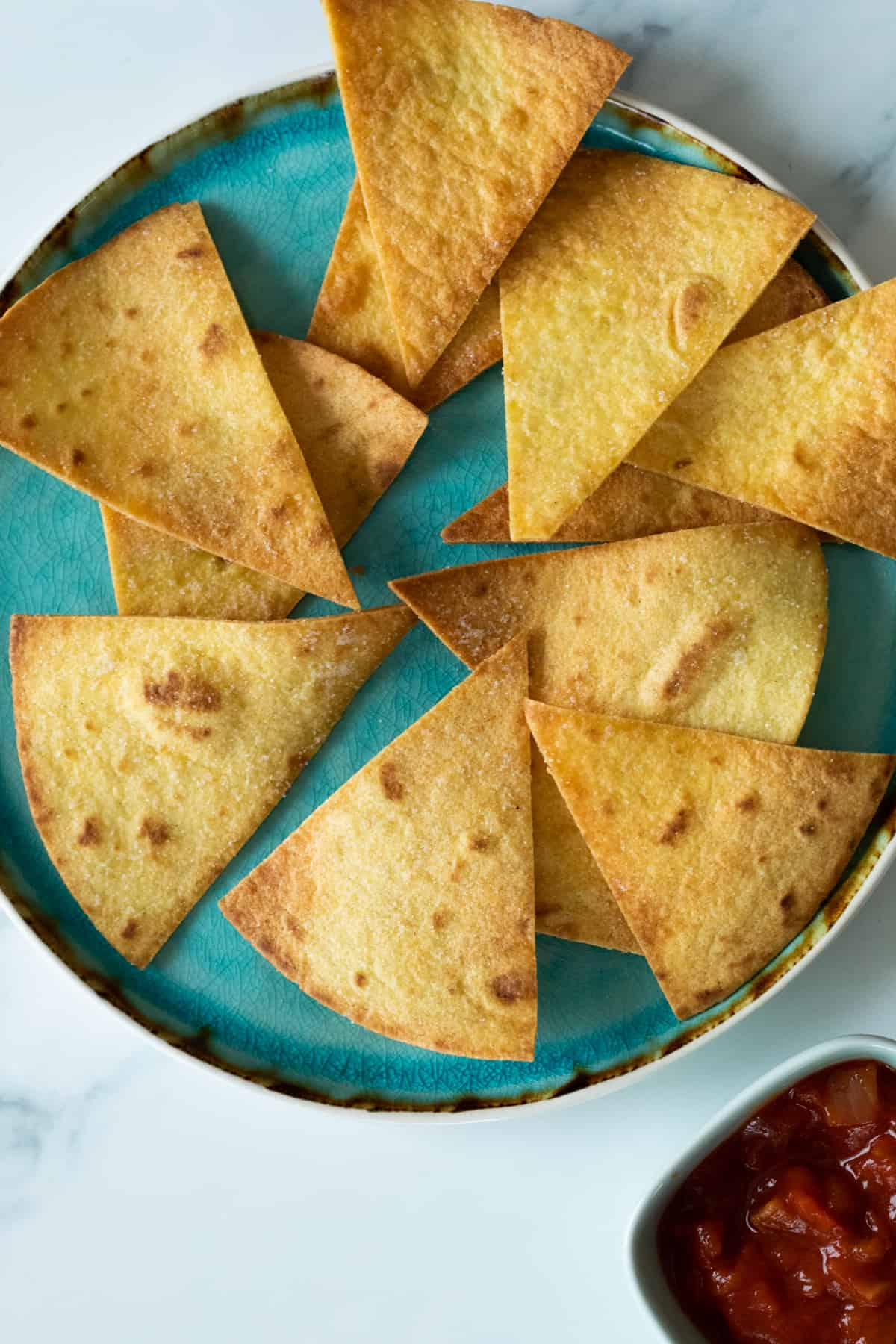 homemade tortilla chips on a blue plate