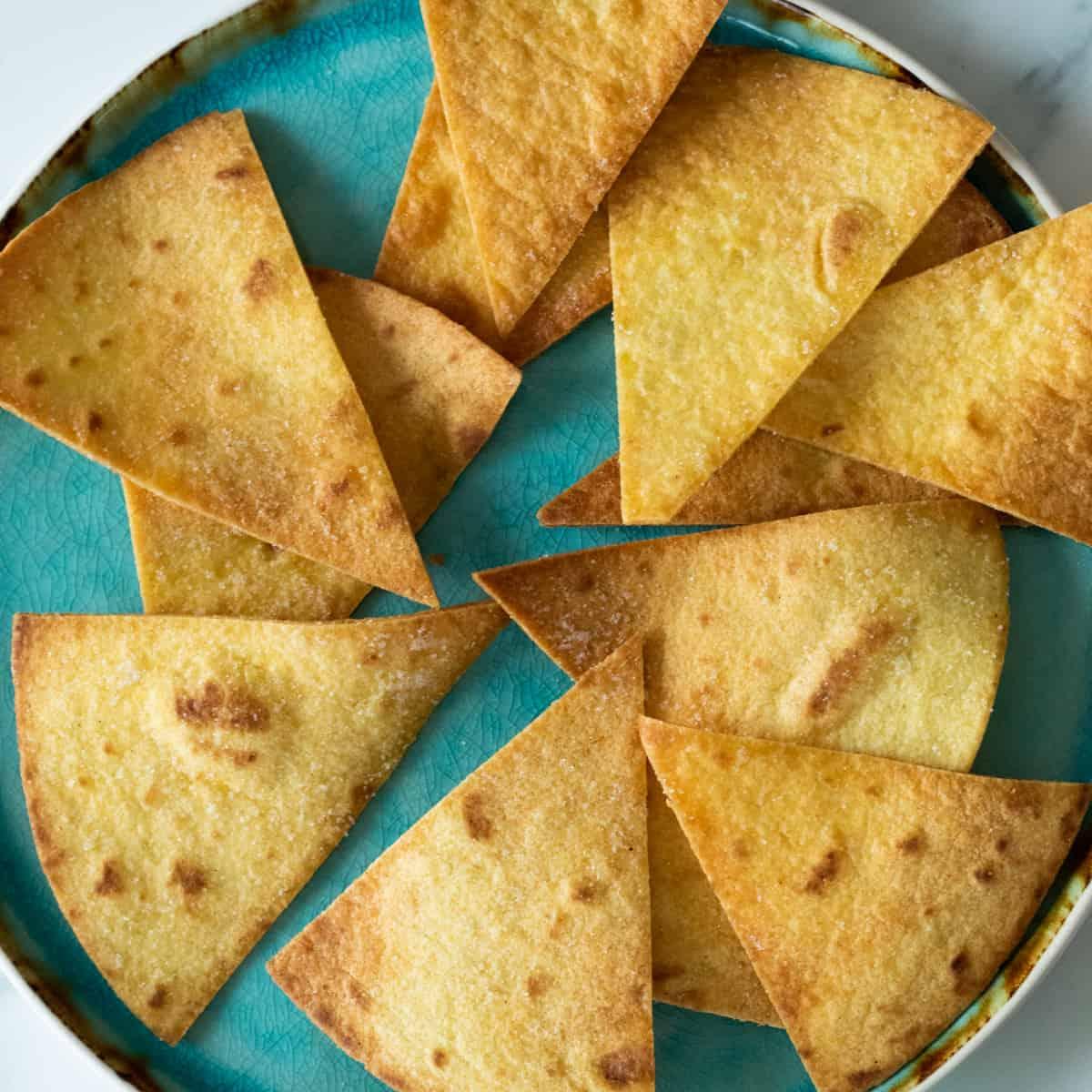 homemade tortilla chips on a blue plate