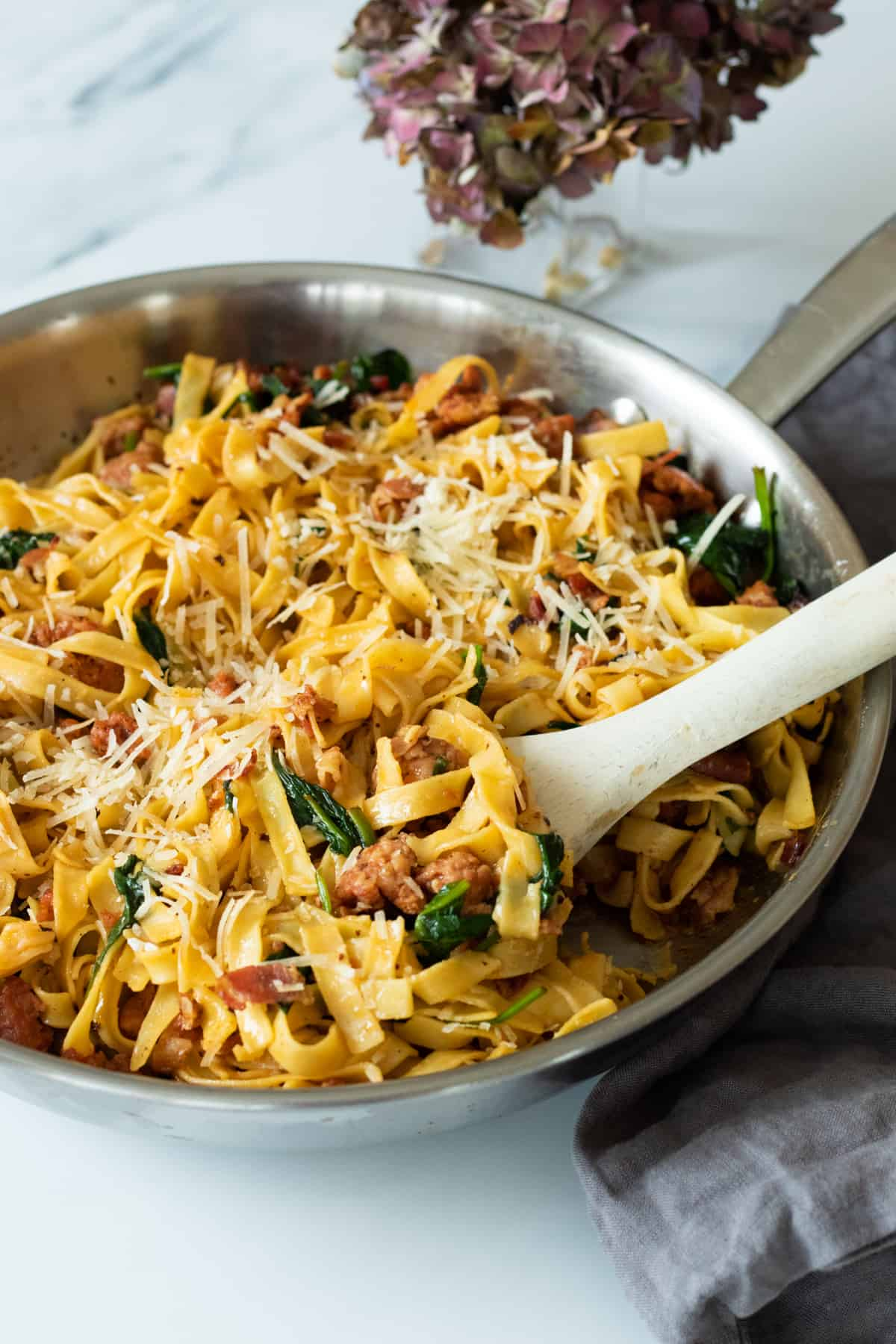 spicy sausage pasta in a pan with a wooden spoon