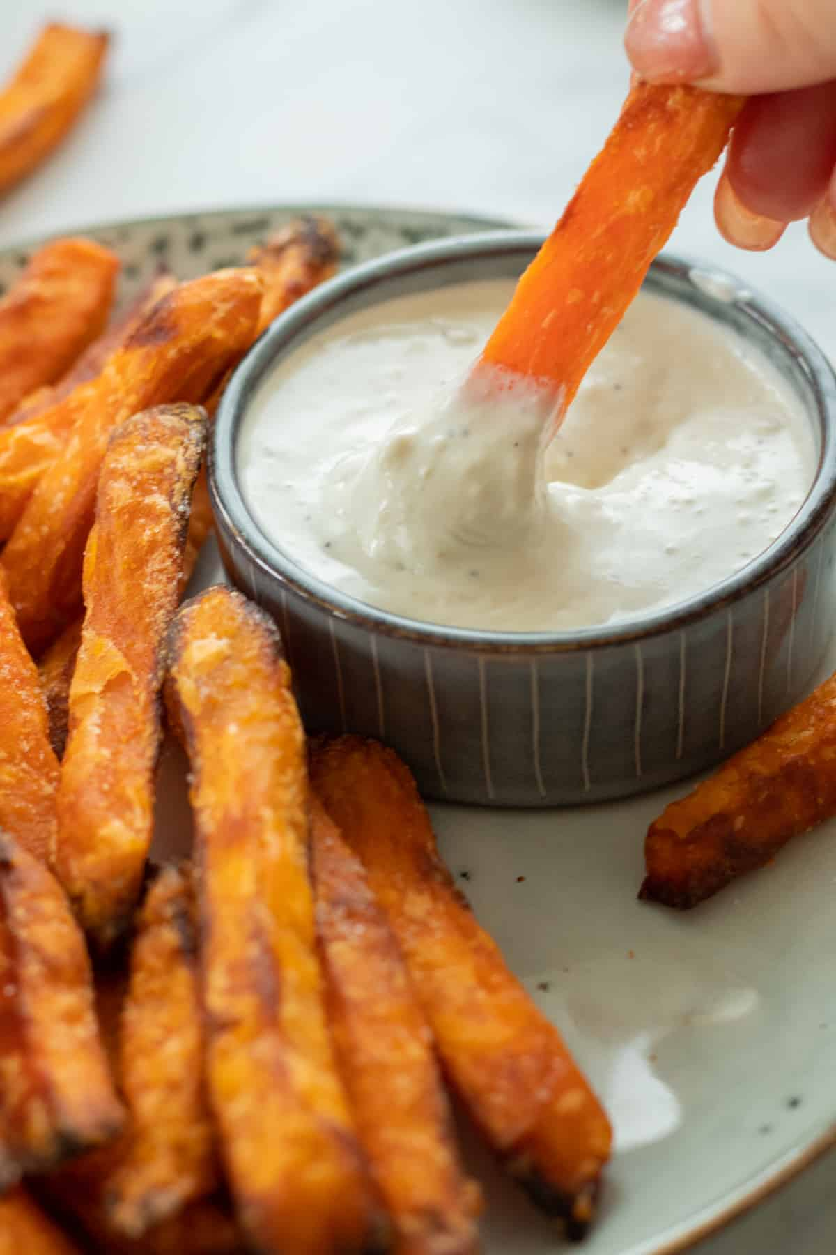 a sweet potato fry being dipped in blue cheese sauce
