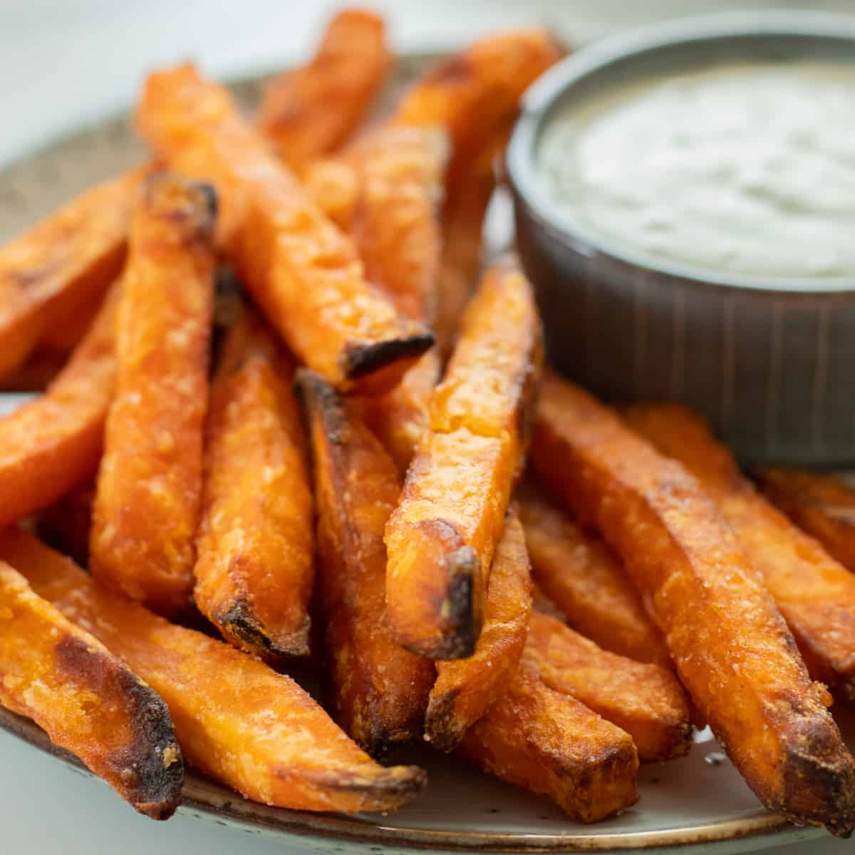 sweet potatoes on a plate next to a dipping sauce