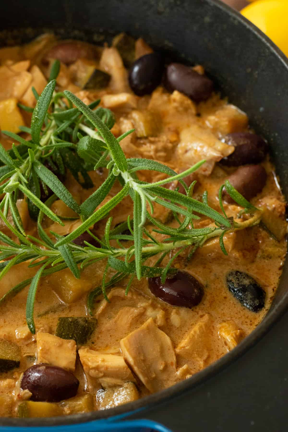 close up of spanish chicken stew topped with rosemary