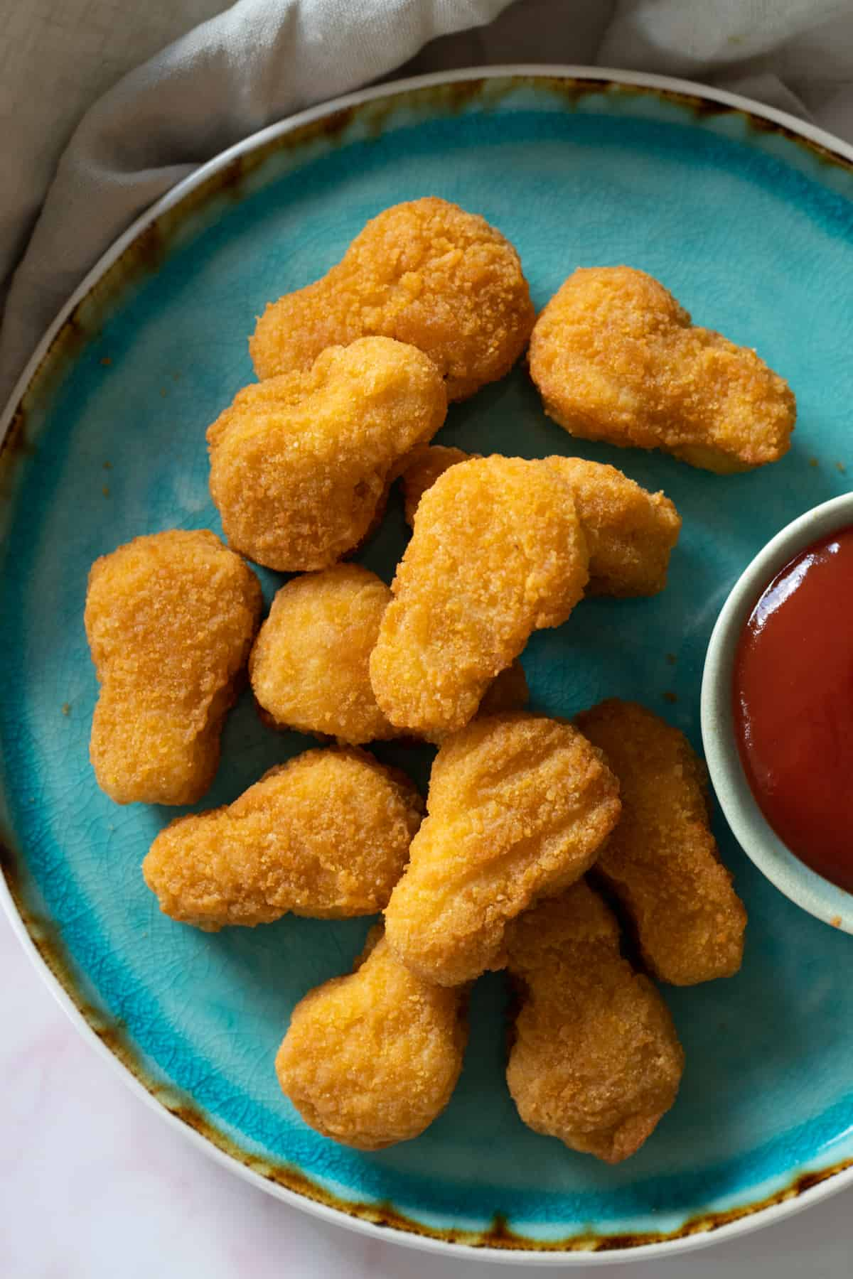 chicken nuggets on a plate with a bowl of ketchup