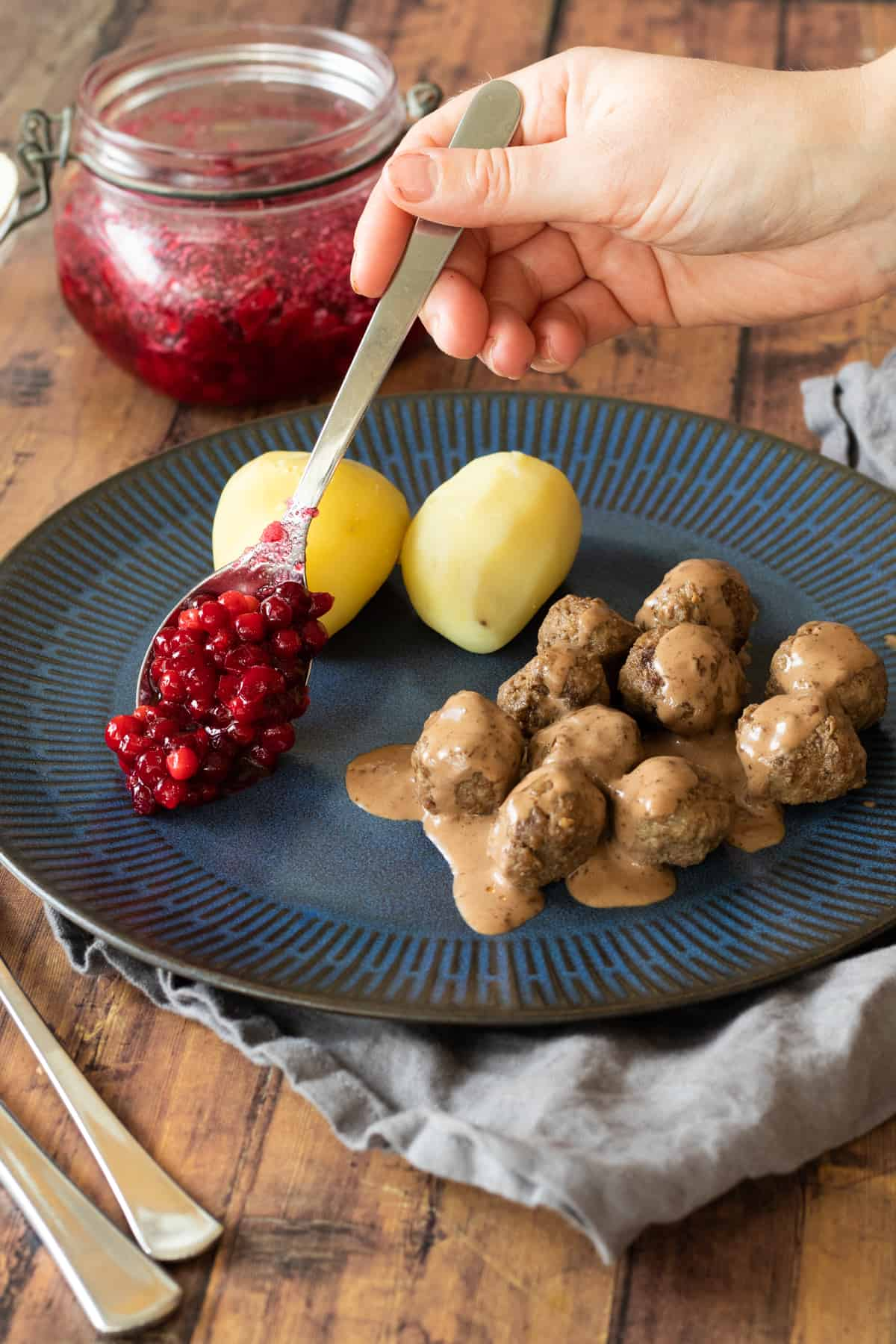meatballs, potatoes and lingonberries on a blue plate