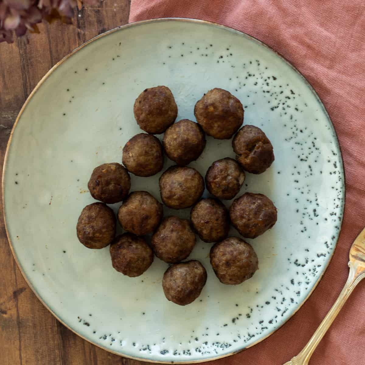 frozen meatballs cooked in air fryer on a blue plate