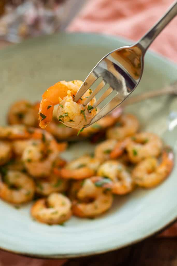 air fryed shrimp with parsley on a blue plate