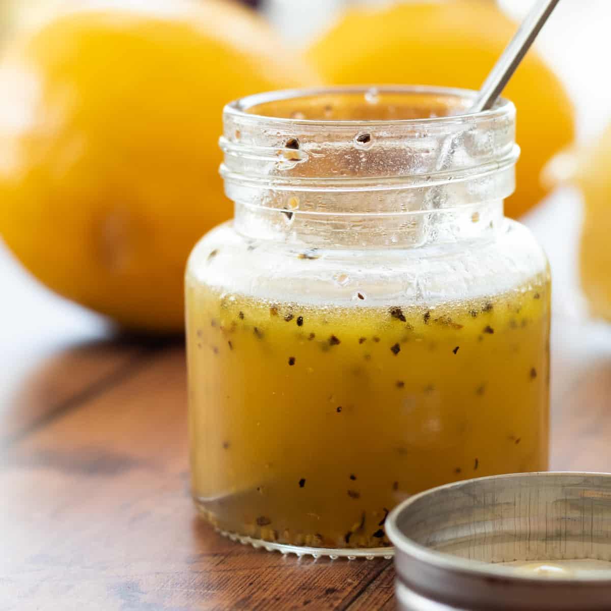 honey lemon vinaigrette in a jar with a spoon
