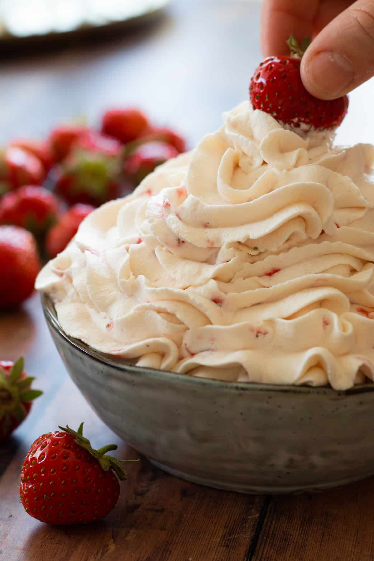 strawberry whipped cream in a bowl topped with a strawberry