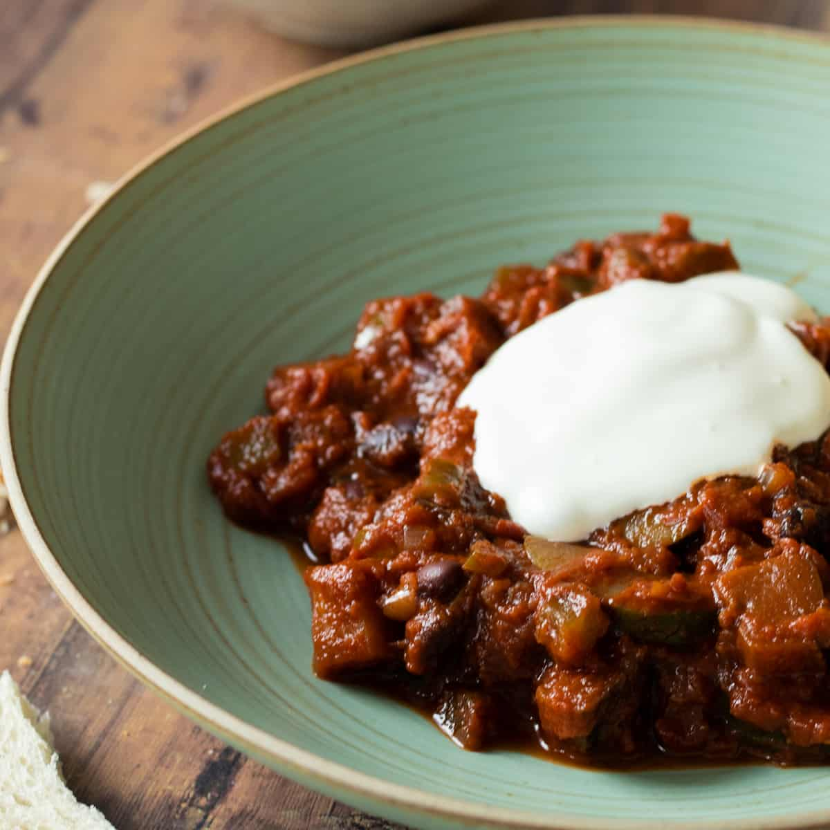 vegetarian chili sin carne on a green plate with crème fraîche and bread